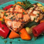 Marinated chicken and salmon over vegetables