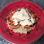 Seared chicken over rice topped with thyme cream sauce